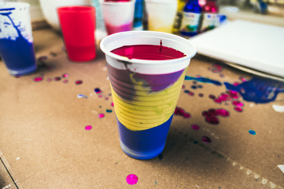 A cup with mixed colours for the Dirty Pour technique of Acrylic Pouring.