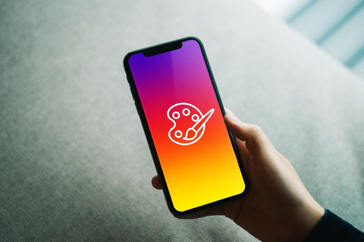 Hand hält ein Iphone, auf dem das perfekte Instagram-Profil für Künstler zu sehen ist
